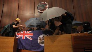 Des manifestants sont entrés dans l'hémicycle du Parlement local de Hong Kong, lundi 1er juillet. Ils ont déployé un drapeau de l'époque britannique et ont recouver le symbole actuel avec de la bombe de peinture noire. (VIVEK PRAKASH / AFP)