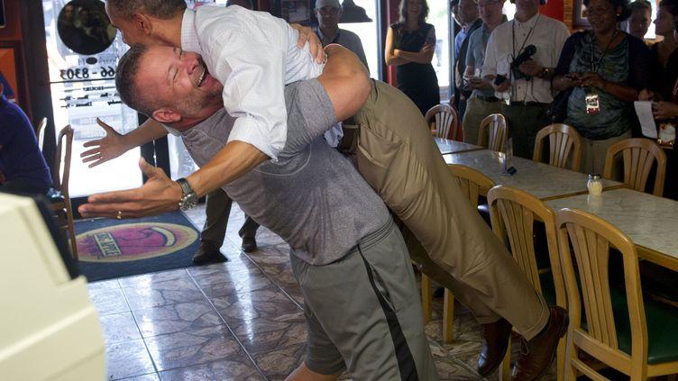 En visite à Fort Pierce, en Floride, le 9 septembre 2012, le président des Etats-Unis, Barack Obama, laisse le propriétaire d'une pizzeria locale le soulever de terre. (SAUL LOEB / AFP)
