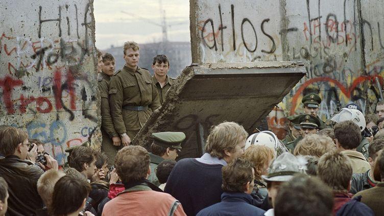 Des habitants de Berlin-Ouest observent des soldats d'Allemagne de l'Est démolir le mur de Berlin, le 11 novembre 1989. (GERARD MALIE / AFP)