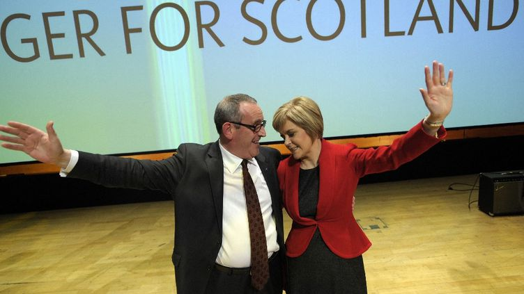 La nouvelle dirigeante du Parti national écossais Nicola Sturgeon et Christian Allard, membre du Parlement écossais d'origine française pour le nord-est de l'Écosse saluent le public après qu'elle a prononcé son premier discours liminaire à la conférence du SNP à Perth, en Écosse. (ANDY BUCHANAN / AFP)