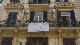 """Une pancarte """"Io resto a casa"""" (Je reste à la maison) affichée à Naples (Italie), le 18 mars 2020. (PAOLO MANZO / NURPHOTO / AFP)"""