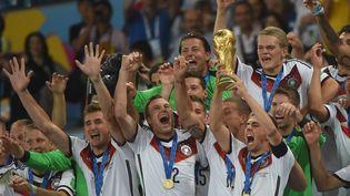 La Mannschaft remporte la Coupe du monde et lecapitaine allemand Philipp Lahm soulève le trophée entouré de ses coéquipiers, dimanche 13 juillet, à Rio (Brésil). (PATRIK STOLLARZ / AFP)