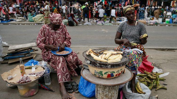 Des femmes vendant de la banane braisée au bord de la route, à Abidjan (Côte d'Ivoire), le 13 août 2019. (MAHMUT SERDAR ALAKUS / ANADOLU AGENCY)