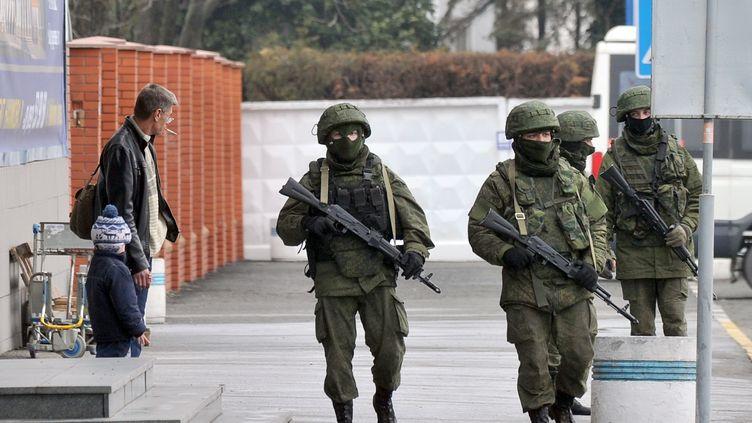 Des hommes armés patrouillent autour de l'aéroport de Simferopol, le 28 février 2014, en Crimée (Ukraine). (GENYA SAVILOV / AFP)
