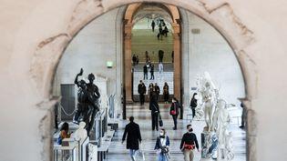 Des visiteurs se promènent dans un couloir du musée du Louvre à Paris, le 19 mai 2021. (ALAIN JOCARD / AFP)