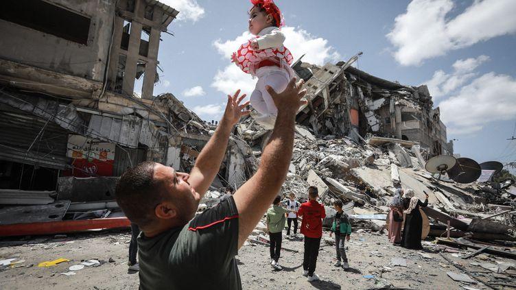 22 mai 2021. Gaza. Un Palestinien joue avec sa petite fille en face de l'immeuble Al-Shuruq détruit par un raid israélien. Le cessez-le-feu établi entre Israël et le Hamas reste fragile. (MAJDI FATHI / NURPHOTO / AFP)