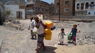Des habitants d'Aden (Yémen) viennent remplir des bidonsd'eau, le 5 avril 2015, dans une ville marquée par des combats et des coupures d'eau. (WAIL SHAIF THABET / ANADOLU AGENCY / AFP)