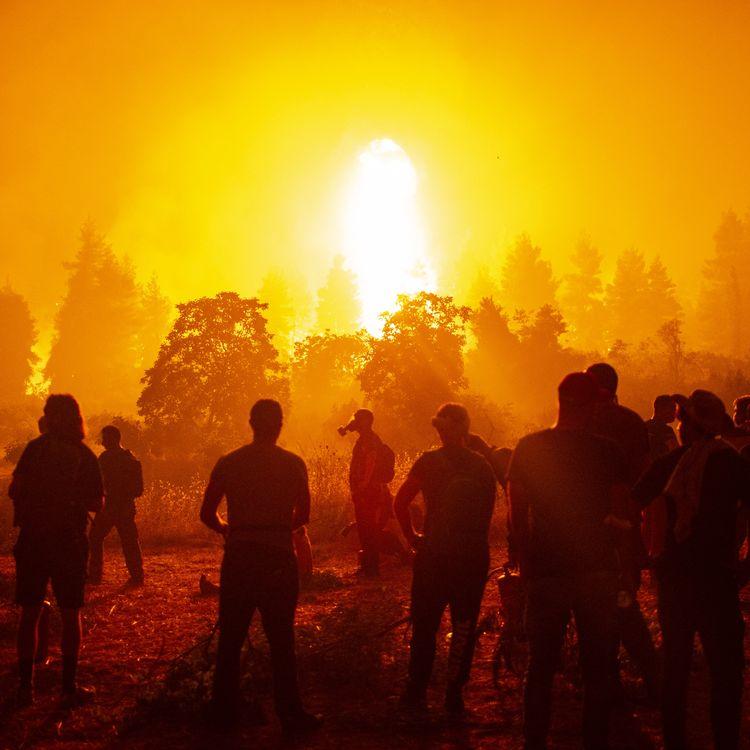 Des jeunes et des volontaires locaux se rassemblent pour soutenir les pompiers lors d'un incendie de forêt à côté du village de Kamatriades, près d'Istiaia, dans le nord de l'île d'Eubée (Grèce), le 9 août 2021. (ANGELOS TZORTZINIS / AFP)