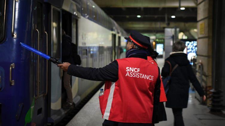 Un agent SNCF oriente les passagers à la gare Montparnasse, à Paris, le 11 décembre 2019. (ALAIN JOCARD / AFP)