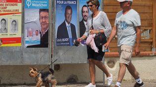 Des habitants passent devant des affiches pour les élections législatives à Saint-Cyprien (Pyrénées-Orientales), le 6 juin 2017. (RAYMOND ROIG / AFP)