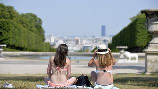 Deux femmes profitent du soleil à Saint-Cloud (Hauts-de-Seine), le 1er juillet 2015. (MIGUEL MEDINA / AFP)