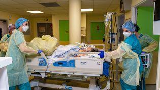 Des soignantes transportent une personne au sein du service d'urgence et de réanimation de l'hôpital Saint-Camille de Bry-sur-Marne (Val-de-Marne) le 29 avril 2020. (ALINE MORCILLO / HANS LUCAS / AFP)