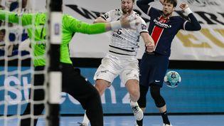 Harald Reinkind (THW Kiel) face au gardien du PSG Yann Genty lors du quart de finale aller de Ligue des champions, le 12 mai 2021. (FRANK MOLTER / DPA)