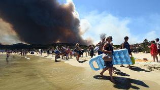 Les vacanciers quittent la plage alors qu'un feu ravage la forêt de Bormes-les-Mimosas en Provence Alpes Côte d'Azur, le 26 juillet 2017. (ANNE-CHRISTINE POUJOULAT / AFP)
