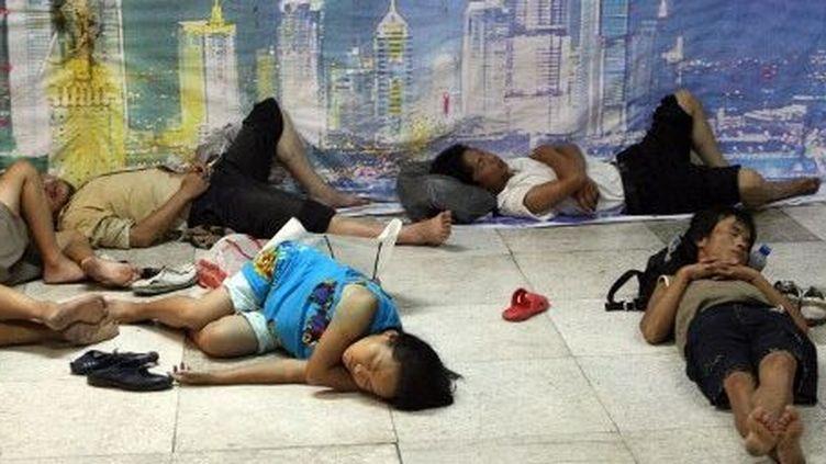 Des mingong s'abritant près d'une bouche d'air conditionné dans le métro, à Shanghai, en 2007. (AFP/MARK RALSTON)