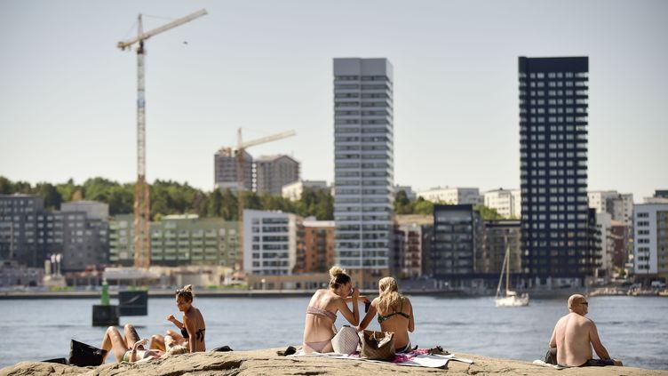 Au cœur de Stockholm (Suède) des gens se font bronzer, le 16 juin 2018. Depuis plusieurs semaines, le pays connaîtun épisode de chaleur exceptionnel. (HOSSEIN SALMANZADEH / AFP)