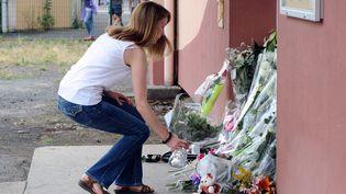 Une femme dépose des fleurs devant l'école Edouard-Herriot, à Albi (Tarn), le 5 juillet 2014. (REMY GABALDA / AFP)