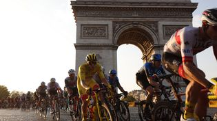 Tadej Pogacar, en jaune, au pied de l'Arc de Triomphe. (Kenzo Tribouillard / AFP)