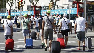 Des touristes se promènent dans les rues de Barcelone (Espagne),le 28 juin 2015. (QUIQUE GARCIA / AFP)