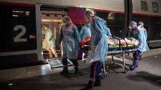 Le personnel médical transporte un patient infecté par le coronavirus dans unTGV médicalisé à la gare d'Austerlitz à Paris, avant son évacuation, avec 35 autres patients vers des hôpitaux de Bretagne, le 1er avril 2020. (THOMAS SAMSON / POOL)