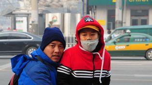 Un enfant porte un masque en raison de la pollution de l'air, à Pékin (Chine), le 28 novembre 2015. (MAHMUT ATANUR / ANADOLU AGENCY / AFP)