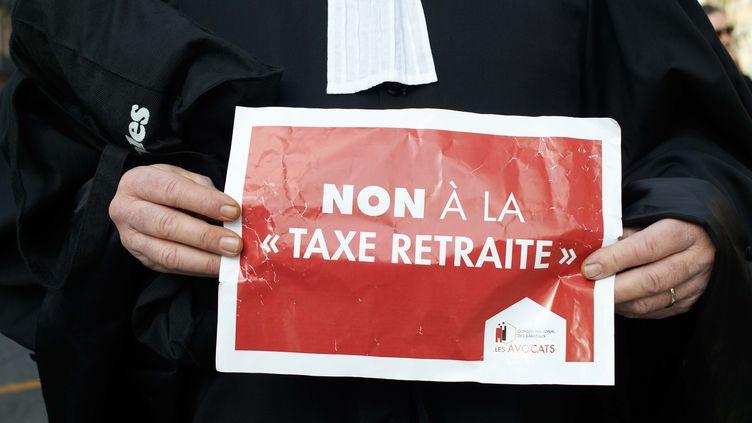 Un avocat avec une pancarte pour protester contre la réforme des retraites. (ALAIN PITTON / NURPHOTO)
