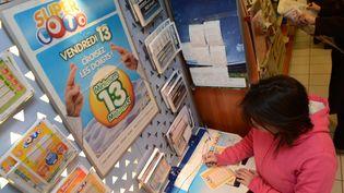 Une femme remplit un ticket de Loto, à Angers (Maine-et-Loire), jeudi 12 décembre 2013. (MAXPPP)