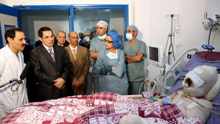 Le président Ben Ali au chevet de Mohamed El Bouazizi, qui s'est immolé par le feu, à Tunis, le 28/12/2010 (AFP/TUNISIA PRESIDENCY)