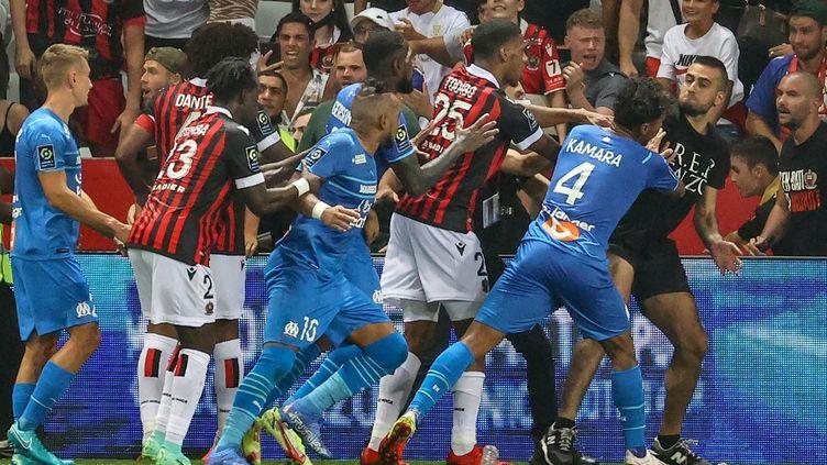 Des supporters niçois ont envahi le terrain et en sont venus aux mains avec les joueurs marseillais. (VALERY HACHE / AFP)