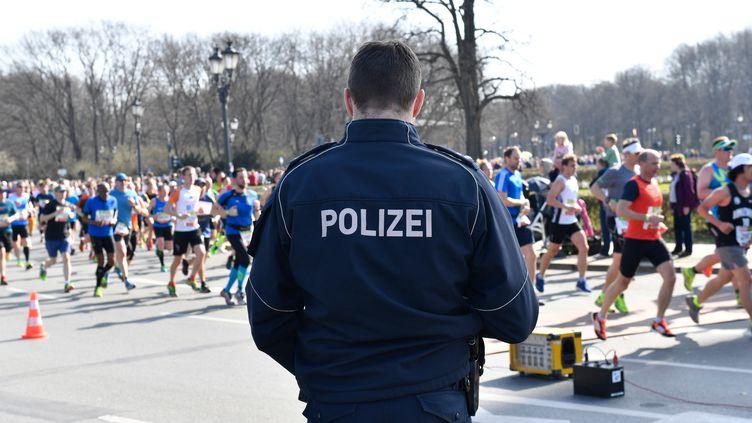 Un policier surveille le semi-marathon de Berlin (Allemagne), le 8 avril 2018. (PAUL ZINKEN / DPA / AFP)