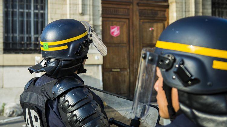 Des CRS montent la garde devant la caserne où se sont réfugiés les migrants, le 11 juin 2015 à Paris. (GEOFFROY VAN DER HASSELT / ANADOLU AGENCY / AFP)