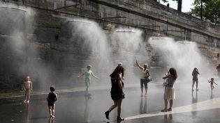 Des passants se rafraîchissent sous des brumisateurs à Paris Plage, en 2013. (MANUEL COHEN / AFP)