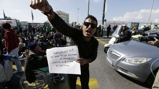 Un réfugié syrien demande l'ouverture de la frontière lors d'une manifestation dans le port de l'Athènes du Pirée, le 26 février 2016. (THANASSIS STAVRAKIS / AP / SIPA)