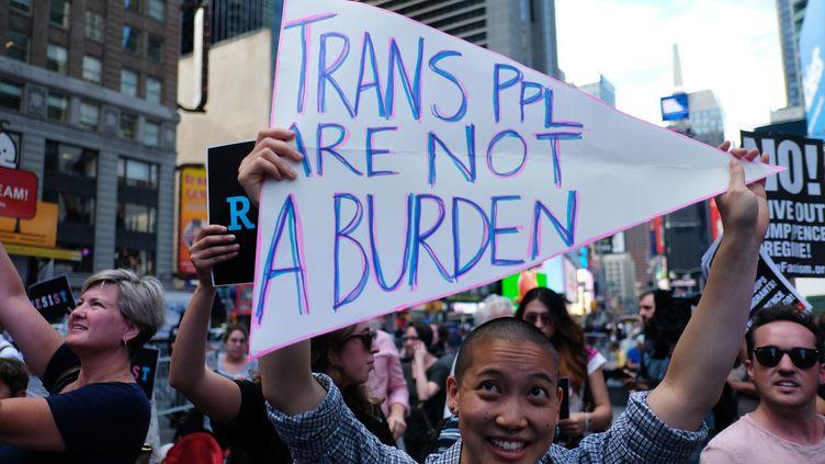 """Manifestation à New York, le 26 juillet 2017, après les tweets de Donald Trump. Sur la banderole, on peut lire : """"Les personnes transgenre ne sont pas une charge"""". (JEWEL SAMAD / AFP)"""