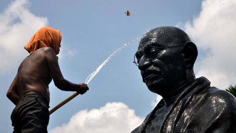Un travailleur nettoie la statue de Mahatma Gandhi à Bhubenaswar (Inde), le 1er octobre 2015. (ASIT KUMAR / AFP)