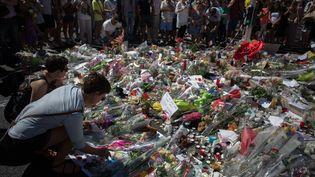 Des habitants déposent des fleurs sur la promenade des Anglais à Nice (Alpes-Maritimes), en mémoire des victimes de l'attentatdu 14 juillet, le 16 juillet 2016. (IRINA KALASHNIKOVA / SPUTNIK / AFP)