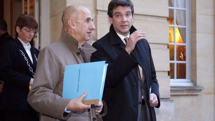 Louis Gallois (G) proposait de transférer une part des charges patronales et syndicales sur la fiscalité. Le ministre du Redressement productif, Arnaud Montebourg(D), pencherait pour un crédit d'impôt accordé aux entreprises, selon Le Point et l'AFP. (PIERRE VERDY / AFP)