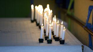 Des bougies allumées à la mémoire des victimes de l'accident de car de Puisseguin (Gironde), le 24 octobre 2015. (JEAN-PIERRE MULLER / AFP)