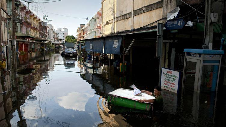 Un homme se cramponne à son radeau de fortune dans les rues inondées de Bangkok (Thaïlande), le 30 octobre 2011. (NICOLAS ASFOURI / AFP)