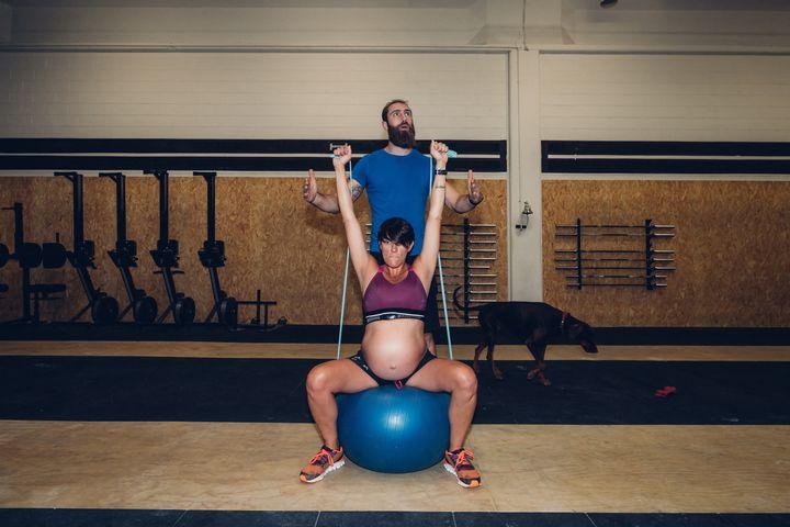 Un entraîneur guide une femme enceinte à l'aide de cordes dans une salle de sport. (EUGENIO MARONGIU / CULTURA CREATIVE / AFP)