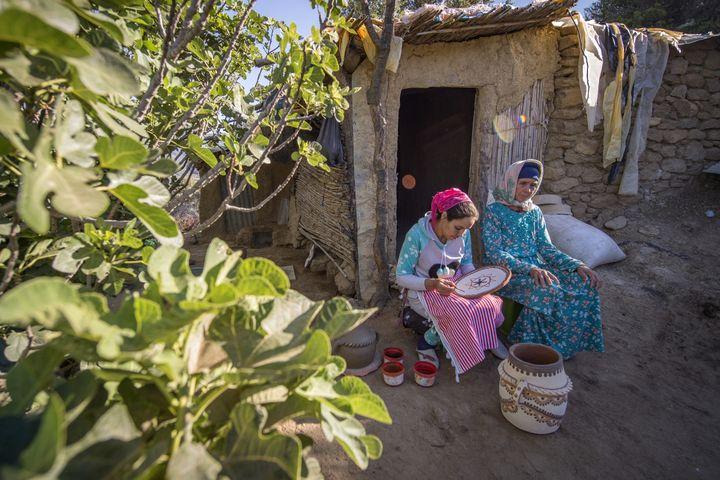 La potière marocaine Houda Oumal (à gauche) peint avec des pigments naturels sur l'une de ses poteries, sous le regard de sa mère Fatima Harama, près du village d'Ourtzagh dans la région de Taounate le 11 juin 2019. (FADEL SENNA / AFP)