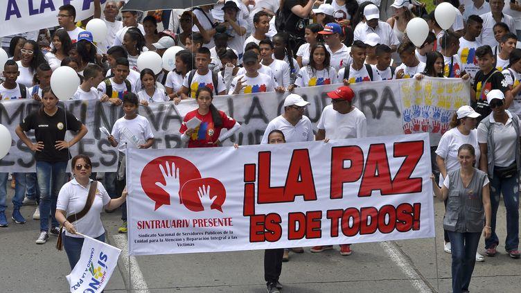 Des manifestants défilent dans les rues de Cali (Colombie) pour un accord de paix entre les Farc et le gouvernement, le 9 octobre 2016. (LUIS ROBAYO / AFP)