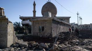 A Mossoul, en novembre 2016, des habitants passent devant une mosquee touchée par des frappes aeriennes dans un quartier du nord est dela ville irakienne. (MAXPPP)