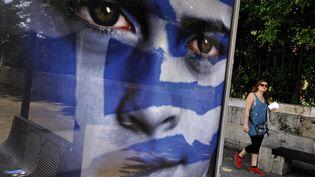 Des Grecs passent derrière les affiches du parti de l'Alliance démocratique (centre) pour les élections législatives du 6 mai,à Athènes, le 3 mai 2012. (LOUISA GOULIAMAKI / AFP)