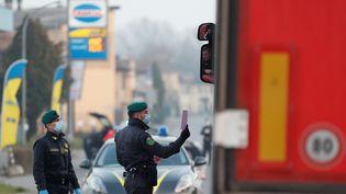 Des membres de la police douanière et financière italienne, portant des masques de protection contre le nouveau coronavirus, contrôlent un véhicule àCasalpusterlengo (Italie), le 24 février 2020. (YARA NARDI / REUTERS)