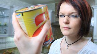 Une femme lit la liste des ingrédients d'une boîte de conserve pour vérifier qu'elle ne comporte aucun produit allergène. (PHILIPPE TURPIN / MAXPPP)