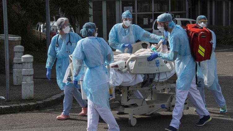 Le personnel médicaldéplace un patient vers un hélicoptère médical à l'hôpital Emile Muller à Mulhouse (Haut-Rhin), le 22 mars 2020 (photo d'illustration). (SEBASTIEN BOZON / AFP)