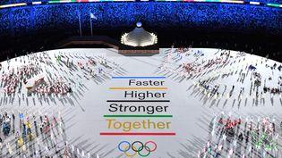 """La devise des Jeux Olympiques, """"plus vite, plus haut, plus fort, ensemble"""", au centre du stade olympique de Tokyo, lors de la cérémonie d'ouverture des Jeux, le 23 juillet. (FRANCOIS-XAVIER MARIT / AFP)"""