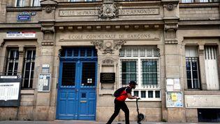Un adolescent passe entrottinette devant une école élémentaire fermée pour cause de confinement, à Paris le 24 avril 2020. (THOMAS COEX / AFP)
