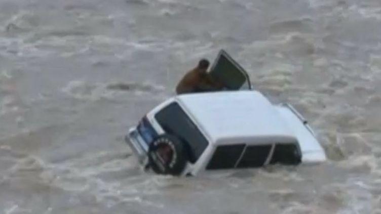 Un conducteur s'est trouvé coincé dans son 4x4, mardi 28 octobre, alors qu'il tentait de traverser une rivière en crue à Fengjie (Chine). (REUTERS)